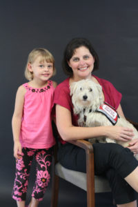 Mother and daughter. Mother is seated with white terrier mix dog in vest in her lap. Child is standing next to mother.