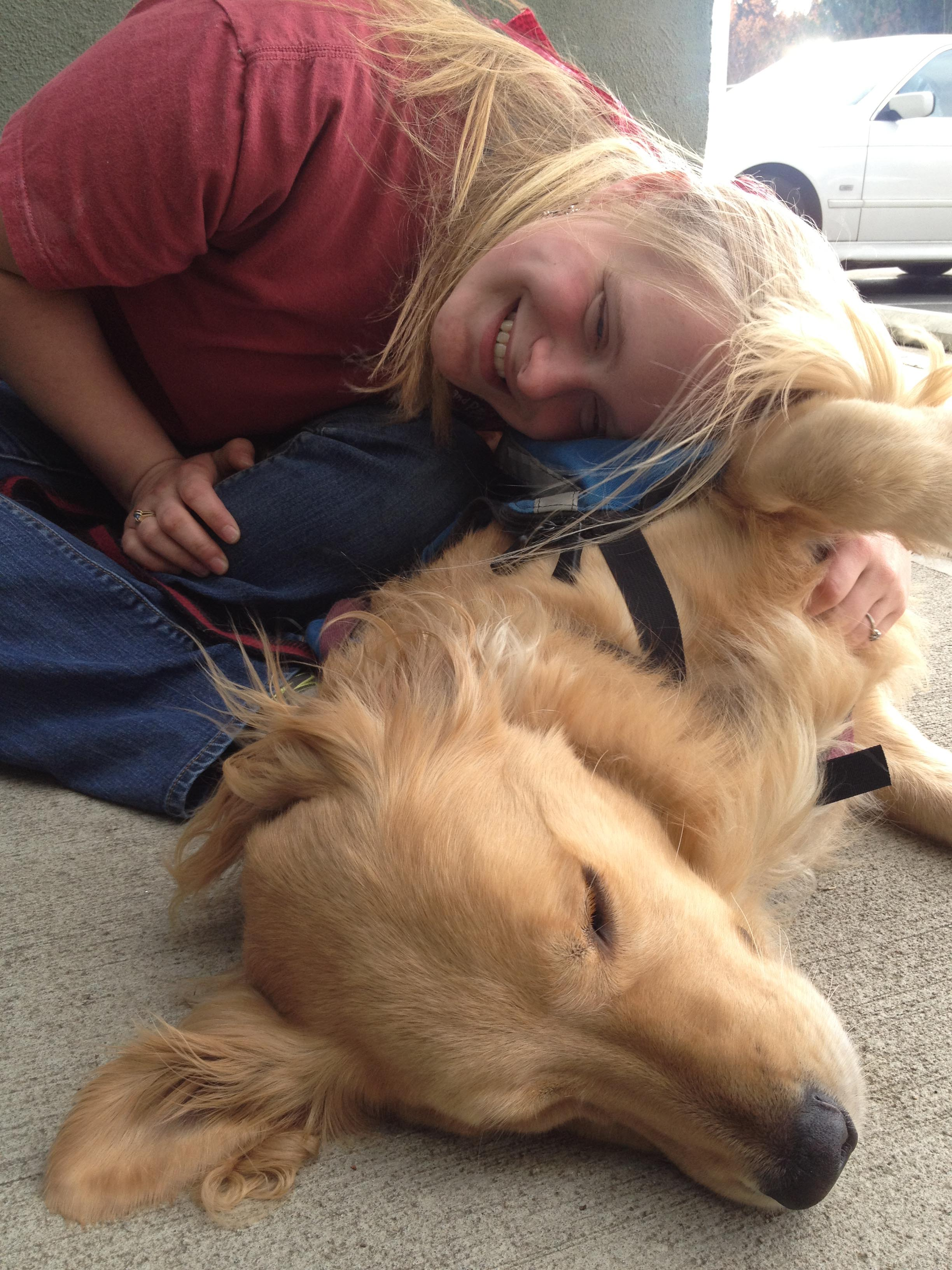 Young woman leaning into her dog and laughing