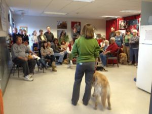 Woman with dog speaking to a group of people in a room