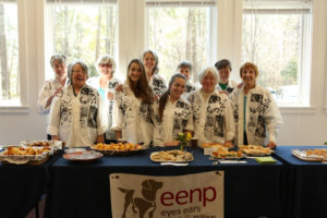 Ten volunteers in matching shirts standing behind a table with food