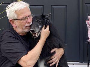 Man in a black shirt with his cheek against a black dog's cheek