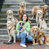Deb Cunningham on steps with dogs around her and a dog in her arms